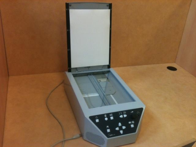 La machine à lire se compose d'une base rectangulaire doté d'un dispositif de type scanner, et d'un capot à rabattre sur le document. Un tableau de bord avec de larges boutons permet de s'en servir facilement.